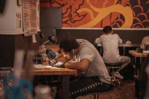 Comienza un aprendizaje de tatuajes: aprendices de tatuajes que trabajan en pieles falsas